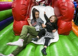 A photo of Emalee and her sister Maya sliding down an inflatable obstacle course.